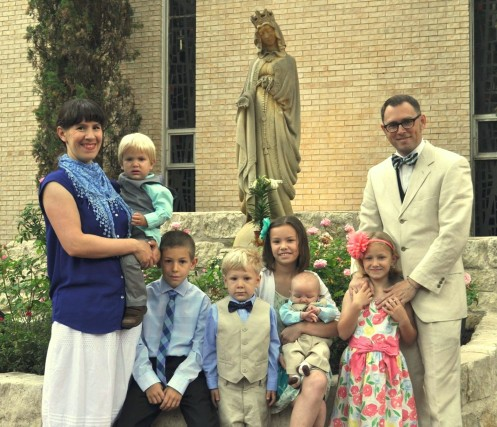 Family before an outdoor statue of the Blessed Mother