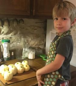 Young boy peeling apples looking at camera