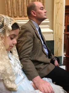 A girl seated wearing a light blue dress and a cream-colored chapel veil, looking down. Her father, in the background, wears a suit and tie and looks forward, covering the girl's left hand with his right.