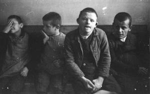 Black and white photo of four boys sitting on a bench. One covers his face, one looks off to the side, two look directly into the camera.
