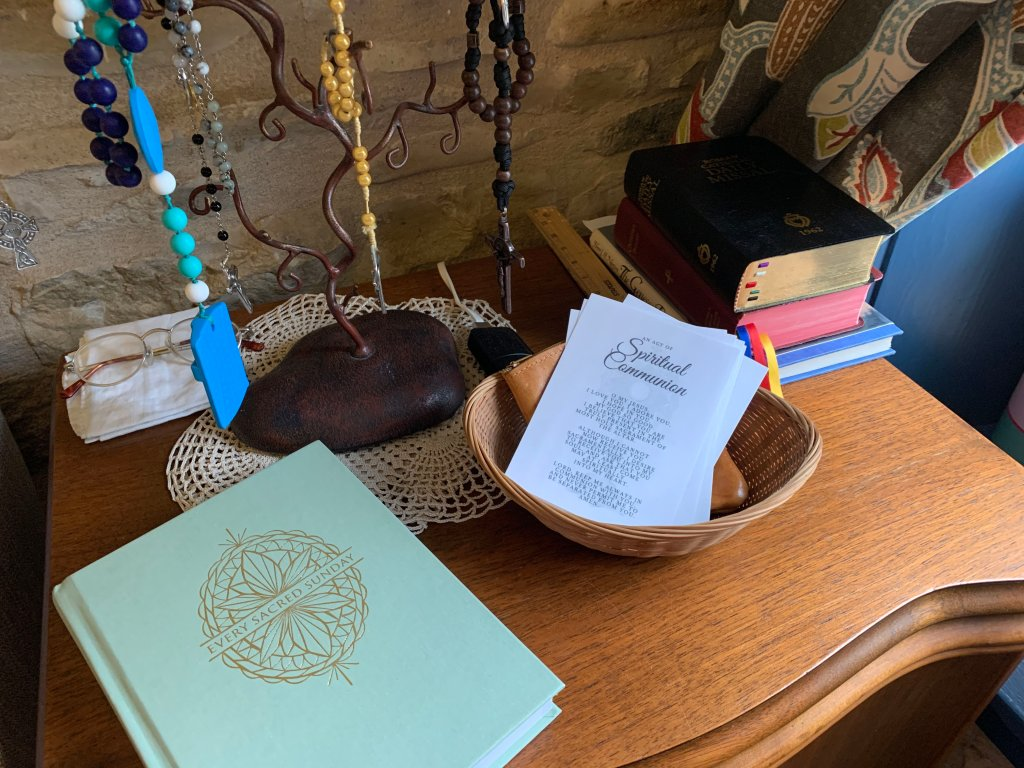 Prayer table with rosaries hanging, Mass journal, spiritual reading, and basket of spiritual communion prayer cards.