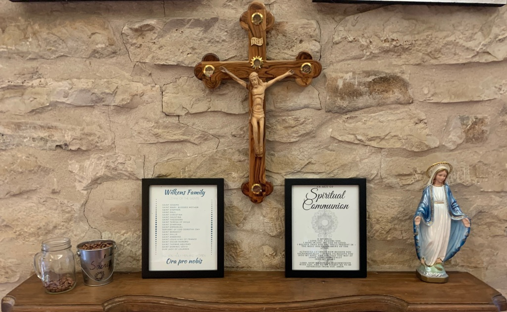 Crucifix hanging above mantel with Lenten sacrifice jar, family saints, spiritual communion prayer, and statue of the Blessed Mother.