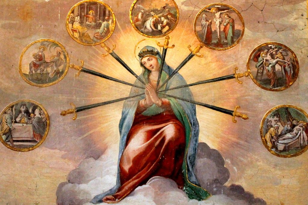 Image: Fresco of the Seven Sorrows of the Blessed Virgin (Tempesta and Circignani, Santo Stefano Rotondo, Rome). Mary wearing a red robe and blue mantle, hands folded in prayer. Seven swords point to her heart. At the hilt of each sword is a small picture of one of the Seven Sorrows meditations.